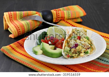 Mexican breakfast of a breakfast taco with eggs and chorizo.  Sides of pico de gallo, avocado, lime and jalapeno.