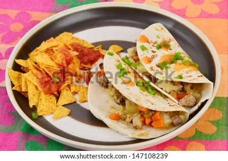 Mexican Burrito - Meat and potatoes with chopped vegetables on flour tortilla.  Garnished with diced jalapeno and spicy sauce; served with chips and salsa on brightly colored floral pattern place mat. - stock photo