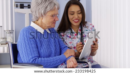 Mexican caregiver sharing tablet with elderly patient - stock photo