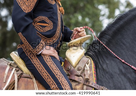 Mexican charro with traditional dress riding - stock photo
