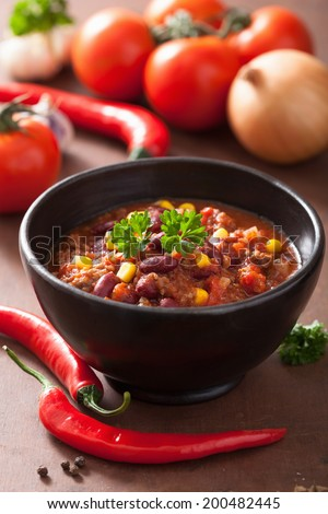 mexican chili con carne in black bowl with ingredients  - stock photo
