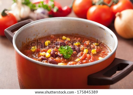mexican chili con carne in red rustic pot with ingredients - stock photo