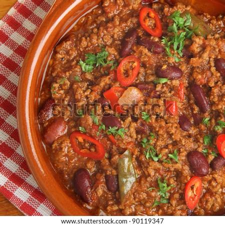 Mexican chilli con carne in terracotta dish. - stock photo