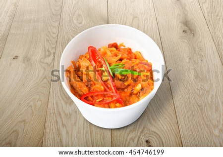 Mexican cuisine food delivery - chili con carne in white plastic plate closeup at natural wood background - stock photo