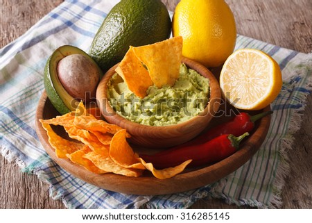 Mexican cuisine: nachos and guacamole sauce and ingredients close-up on the table. horizontal