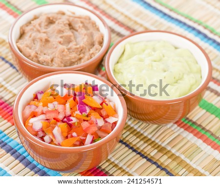 Mexican Dips & Side Dishes - Salsa, Guacamole and Refried Beans. - stock photo