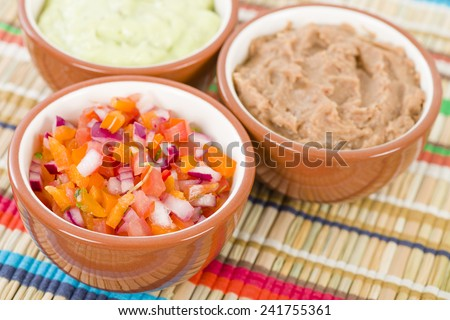 Mexican Dips & Side Dishes - Salsa, Refried Beans and Guacamole.  - stock photo