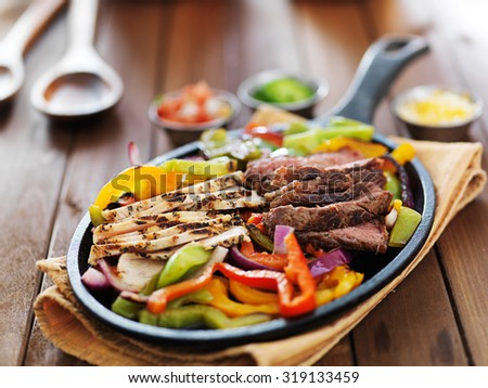 mexican fajita skillet meal with steak and chicken - stock photo