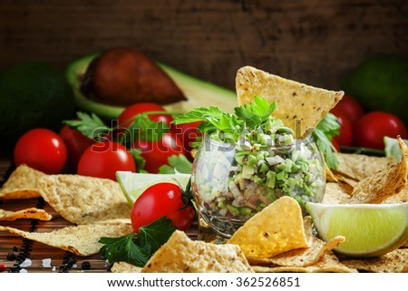 Mexican fast food, corn nachos with guacamole sauce with avocado, red onion and chili peppers, cherry tomatoes, lime and parsley, selective focus - stock photo