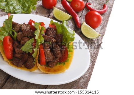 Mexican fast food: tacos stuffed with meat and vegetables - stock photo