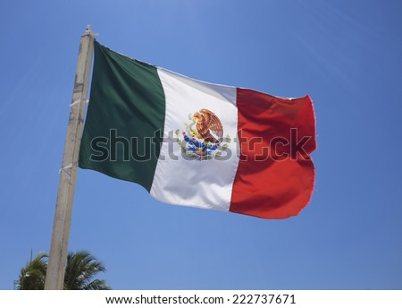 Mexican flag waving on a blue sky.