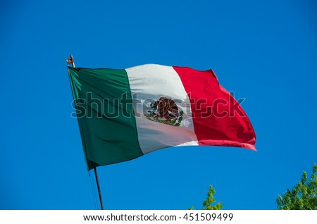 Mexican flag weaving on blue sky - stock photo