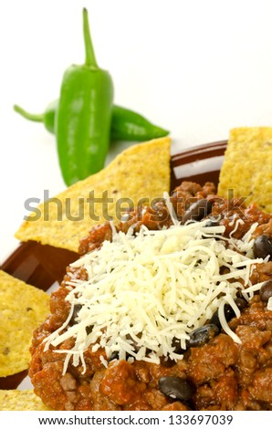 Mexican food: cheesy chili with meat served with nachos - stock photo