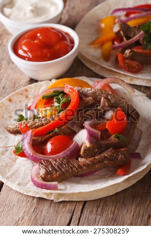 Mexican food: tacos with meat and vegetables close-up. Vertical, rustic style