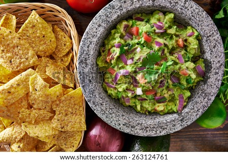 mexican guacamole in molcajete with tortilla chips - stock photo
