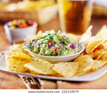 mexican guacamole with tortilla chips and beer - stock photo
