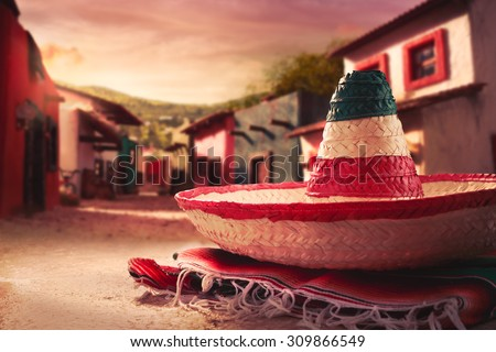 "Mexican hat ""sombrero"" on a ""serape"" in a mexican town at sunset - stock photo"