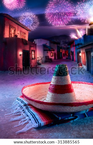 "Mexican hat ""sombrero"" on a ""serape"" in a mexican village at twilight and fireworks - stock photo"