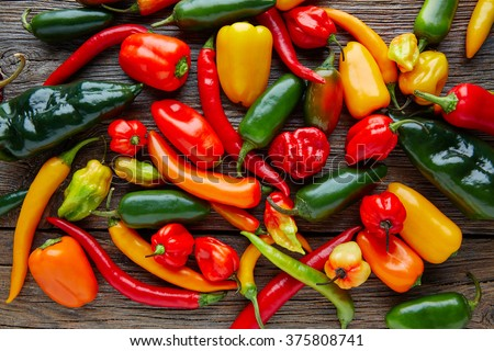 Mexican hot chili peppers colorful mix habanero poblano serrano jalapeno on wood - stock photo