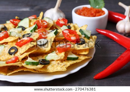Mexican hot nachos with vegetables and chili - stock photo