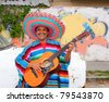 Mexican humor man smiling playing guitar sombrero poncho in street - stock photo