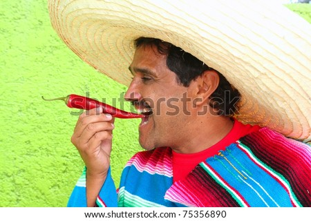 Mexican man poncho sombrero eating red chili hot pepper Mexico - stock photo