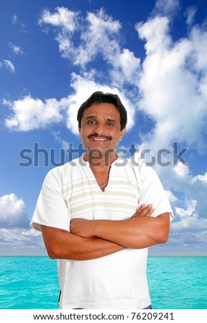 Mexican man with mayan shirt smiling in tropical beach vacation [Photo Illustration] - stock photo
