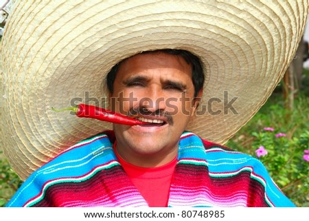 Mexican man with poncho and sombrero eating typical red chili hot pepper in Mexico - stock photo