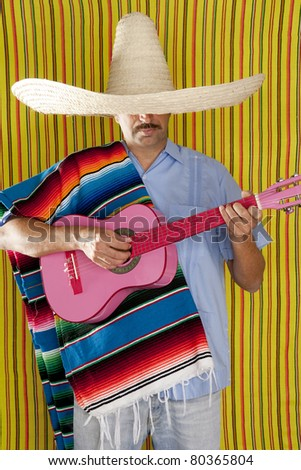 Mexican man with poncho and sombrero playing guitar typical of Mexico - stock photo