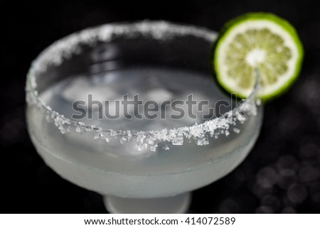Mexican Margarita cocktail macro photo. Focus on salt on side of glass. Black bacground with sea salt spots on it - stock photo