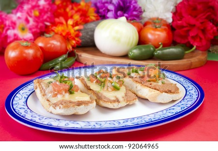 Mexican Molletes Dish. Made with bolillos sliced and spread with beans and topped with cheese. Grilled in an oven until the cheese melts and served with salsa pico de gallo.
