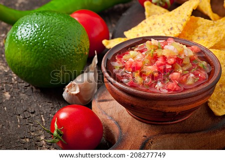 Mexican nacho chips and salsa dip in  bowl on  wooden background - stock photo