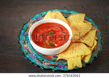 Mexican nachos chips and red salsa dip, on a table with fresh ingredients