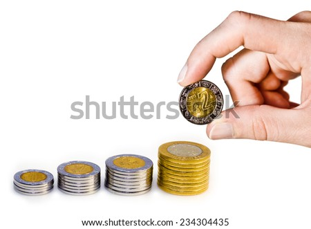 Mexican Peso growth graph represented by hand adding a two Mexican peso coin. - stock photo
