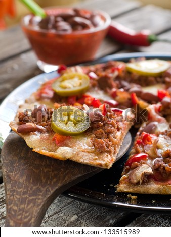 Mexican pizza with minced bean, bean and jalapeno, selective focus