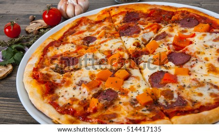 mexican pizza with pepperoni, vegetables, cheese on wood table