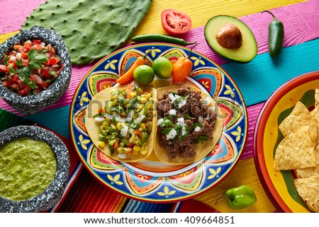 Mexican platillo tacos of barbacoa and vegetarian with sauces and colorful table - stock photo