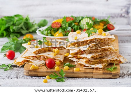 Mexican Quesadilla wrap with chicken, corn and sweet pepper and fresh salad.  - stock photo