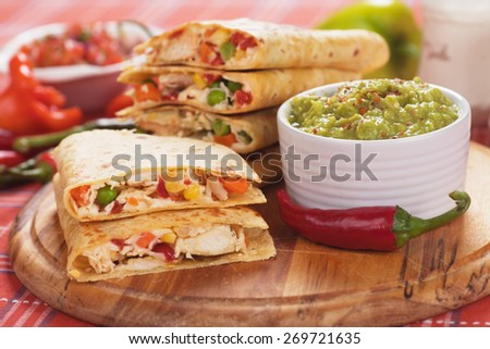 Mexican quesadillas, cheese, meat and vegetable stuffed tortilla with guacamole dip  - stock photo
