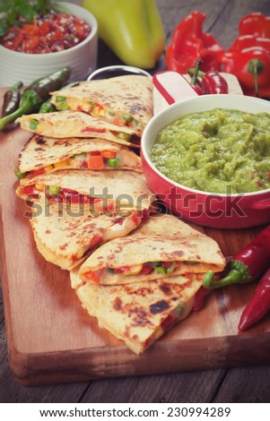 Mexican quesadillas with cheese, vegetable and guacamole dip - stock photo