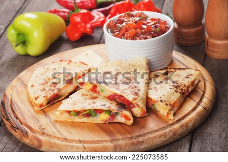 Mexican quesadillas with cheese, vegetables and salsa - stock photo