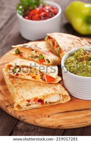 Mexican quesadillas with chicken meat, cheese and vegetables - stock photo