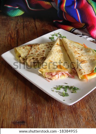 Mexican quesadillas with mushrooms, ham, tomatoes and basil, in a mexican restaurant. - stock photo