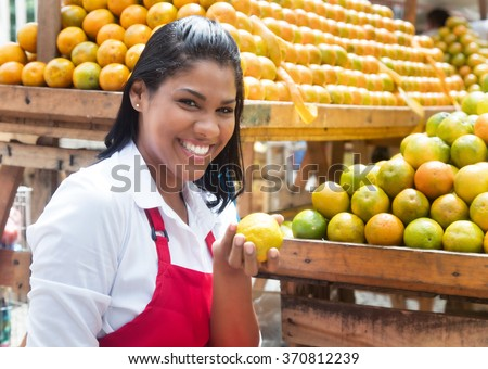 Mexican saleswoman offering oranges on a farmers market - stock photo