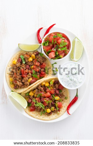 Mexican snack - tortilla with chili con carne and tomato salsa, top view, vertical - stock photo