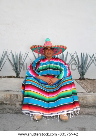 Mexican sombrero smiling man sitting with poncho in front of agave cactus - stock photo