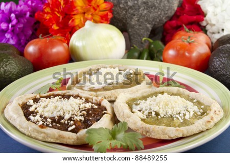 Mexican Sopes Mexican Dish. It is a thick tortilla topped with fried beans, crumbled cheese, red or green salsa and sour cream.
