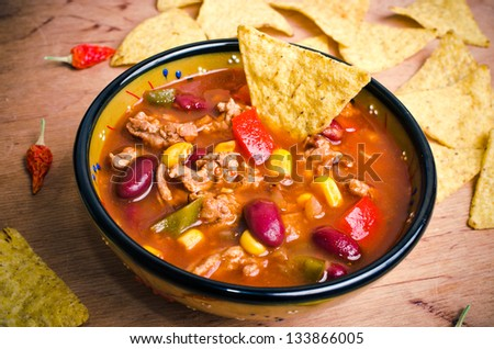 Mexican soup (like chili con carne) with tacos - stock photo