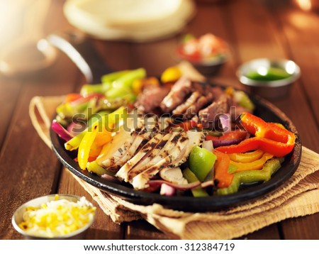 mexican steak and chicken fajitas in iron skillet with bell peppers and onion shot with warm colored light - stock photo