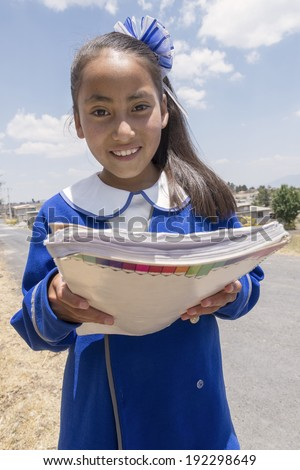 Mexican student showing good grade result  Very proud Mexican young student showing her good grades received in her homework.  - stock photo